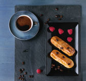 Coffe eclair with raspberries. Ceramic plate with Coffe eclairs with cup of fresh black coffee, raspberries and coffee beans on black slate board over blue Stock Photos