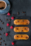 Coffe eclair with raspberries. Coffe eclairs with cup of fresh black coffee, raspberries and coffee beans on black slate board over blue wooden surface. With Royalty Free Stock Photos