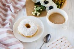 Coffe en een doughnut met verse bloemen stock foto's