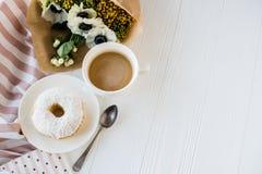 Coffe en een doughnut met verse bloemen stock afbeeldingen