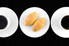 Coffe et croissant d'og de deux cuvettes dans le noir Photographie stock libre de droits