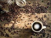Coffe fasole na grunge drewnie z filiżanką zdjęcia stock
