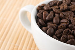 Coffe grains and cup on bamboo mat Royalty Free Stock Images