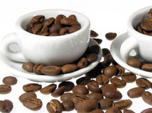 Coffe grayns with cup. Coffee beans and two white cups Stock Photos