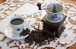 Coffe grinder. Old coffe grinder on wood table with cup o coffee Royalty Free Stock Photo