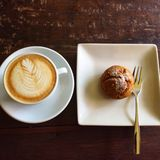 Coffe latte art on wood table. A cup coffee delicious pumpkin bread dessert stock photo