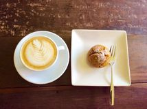 Coffe latte art on wood table. A cup coffee delicious pumpkin bread dessert stock photography