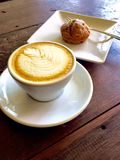 Coffe latte art on wood table. A cup coffee delicious pumpkin bread dessert royalty free stock photo