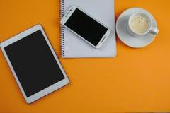 Coffe med minnestavlan, smartphonen och anteckningsboken skyler över brister Arkivfoton