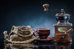 Coffe Mill Cup And Sack With Beans On Mirror Table Stock Image