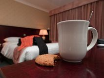 Coffe mug and biscuit in hotel room Royalty Free Stock Image