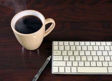 Coffe negro en una taza beige con el teclado en la tabla de madera fotografía de archivo