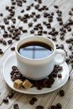 Coffe nero in uno zucchero bianco di canna e della tazza su un piatto su fondo di legno Immagine Stock