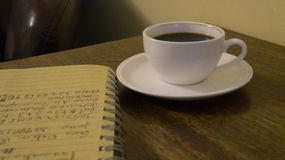 Coffe, notebook and ideas. A Cigar bar whit an espresso, notebook in a leather chair stock images