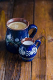 Coffe och Milk i lantliga koppar Arkivfoto