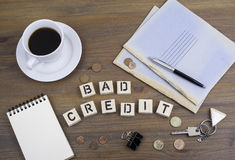 Coffe, pen, money and blocknot on a desk and text Bad Credit.  Stock Images