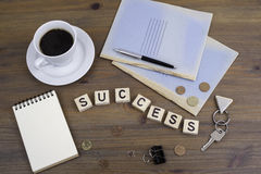 Coffe, pen, money and blocknot on a desk and word Success Royalty Free Stock Image