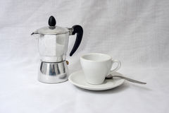 A coffe pot and a cup. An italian coffe maker and a cup stock photography