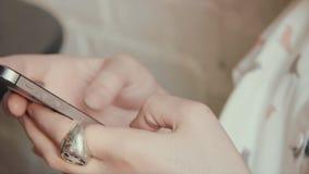 Coffe potable de jeune belle femme heureuse dans le café et textoter à son téléphone intelligent banque de vidéos