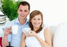 Coffe potable de jeunes couples gais sur le sofa Images stock