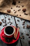 Coffe in red mug on wood table with coffee beans and cinnamon Royalty Free Stock Images