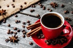 Coffe in red mug on wood table with coffee beans and cinnamon Royalty Free Stock Photos