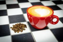 Coffe-Schale mit Bohnen auf Checkedboard Lizenzfreies Stockfoto