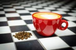 Coffe-Schale mit Bohnen auf Checkedboard Stockbild