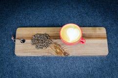 Coffe-Schale mit Bohnen auf hölzerner Platte Stockfoto