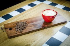 Coffe-Schale mit Bohnen auf hölzerner Platte Lizenzfreie Stockfotografie