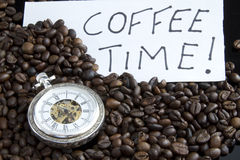 Coffe time. Closeup watch in the Lots of natural coffee beans (coffee time Stock Image