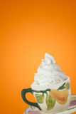 Coffe and Whipped Cream. Whipped cream topping a cup of coffee on an orange background Stock Photography