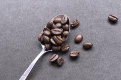 Coffebonen in staallepel Stock Foto