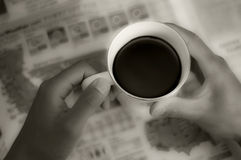 Coffee. Holding a mug of coffee while reading the newspaper Stock Photo