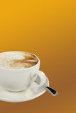 Coffee. Lovely cup of coffee on an orange background royalty free stock photography