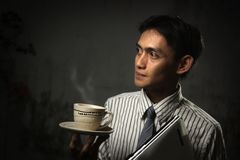 Coffee. Business man holding laptop and coffee stock photography