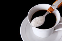 Coffee. Cup of coffee with sugar spoon over black background Stock Photo
