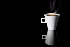 Coffee. A cup of steaming coffee on a reflecting surface Stock Photo