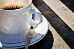 Coffee. Black, foamy coffee in white cup and saucer, with warm morning sunlight shining on setting Stock Photo