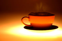 Coffee. Steaming coffee in orange coffee cup Stock Images