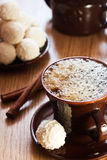 Coffee. Cup of coffee and white chocolate truffles on table Royalty Free Stock Image