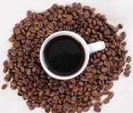 Coffee. White cup with coffee and beans surrounded Stock Images
