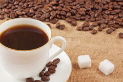 Coffee. Beans and a cup on sacking stock photo