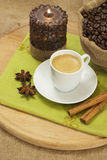 Coffee. Cup of coffee on a wooden board with cinnamon, coffee beans, candle and star anise royalty free stock photo