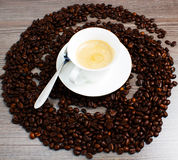 Coffee. Cuo of coffee on wooden table with coffeee beans Royalty Free Stock Images