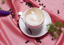 Coffee. Cappuccino in a pink silk backdrop Royalty Free Stock Photo