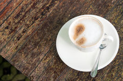 Coffee. A white cup of coffee on the wooden table Royalty Free Stock Image