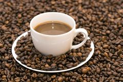 Coffee. Coffe beans in cup on coffee background Royalty Free Stock Images