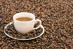 Coffee. Coffe beans in cup on coffee background Stock Photos