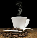 Coffee. Hot coffee in a white cup with beans on wooden background Stock Images